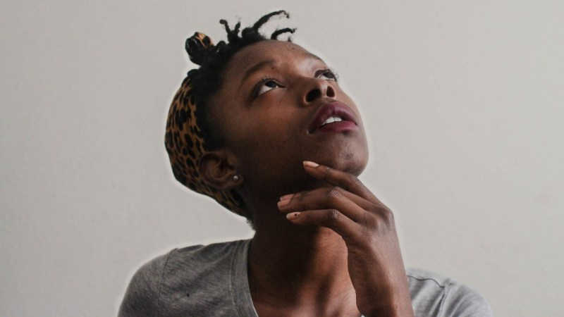 Young black holds her chin up with her left fingers in what appears to be her trying to think or remember