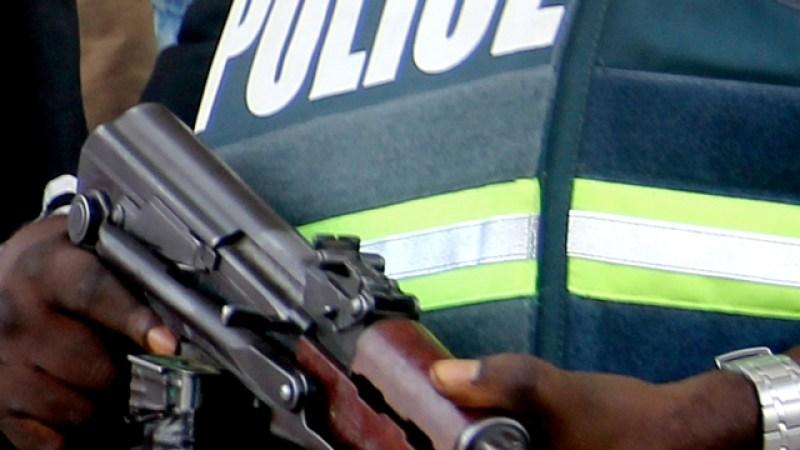 Faceless policeman cradling a gun