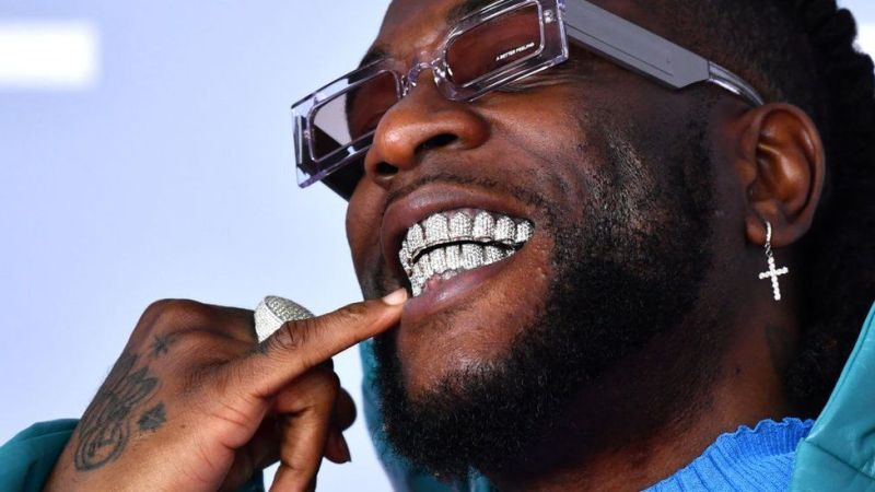 Burna Boy wearing sunshades and touching his lips with his little food