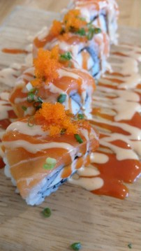 """""""Akuma Roll"""": Salmon slice over a rice covered crab stick"""