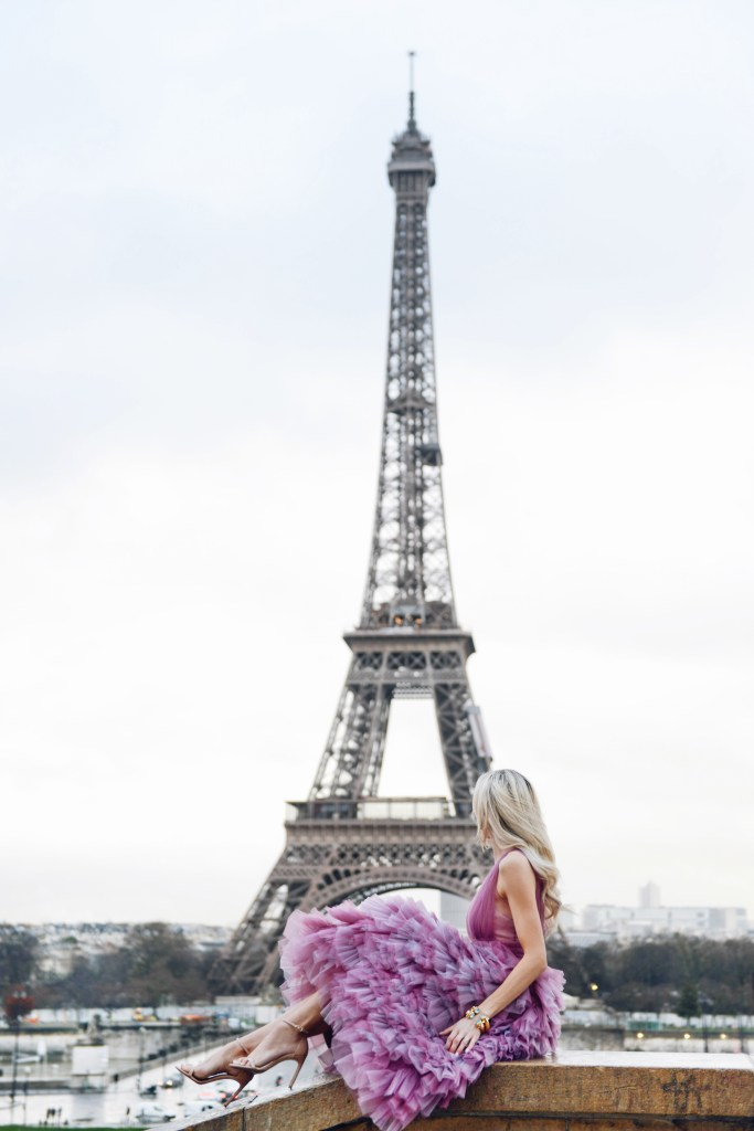 Julie Voss bracelets and earrings, violet marchesa notte gown at eiffel tower in Paris | Top San Francisco fashion blog, Lombard and Fifth, is traveling in Paris and features some Julie Vos jewelry: image of a blonde woman in front of the Eiffel Tower wearing Julie Vos cuff and earrings, Marchesa Notte dress, Alice & Me Clutch, Stuart Weitzman sandals