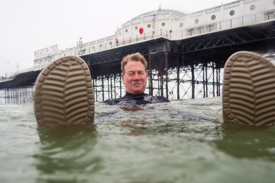 Michael Portillo having a dip in his wetsuit and crocs