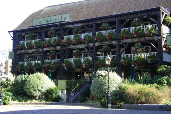 The flowers and balconies on the outside of the Dickens Inn pub