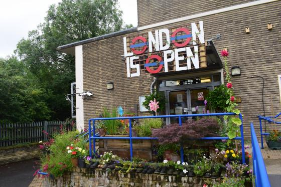 Flowers and Plants by a sign that reads 'London is open'
