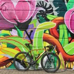 A bicycle propped against a colourful wall