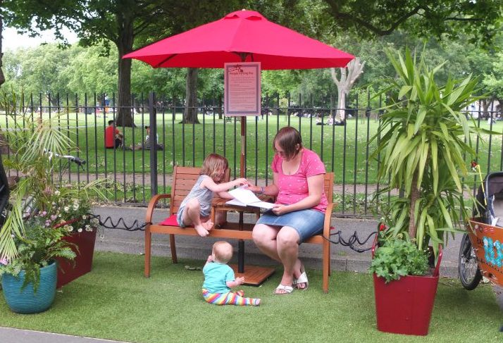 Woman and two children read on a bench in a parklet in Hackney
