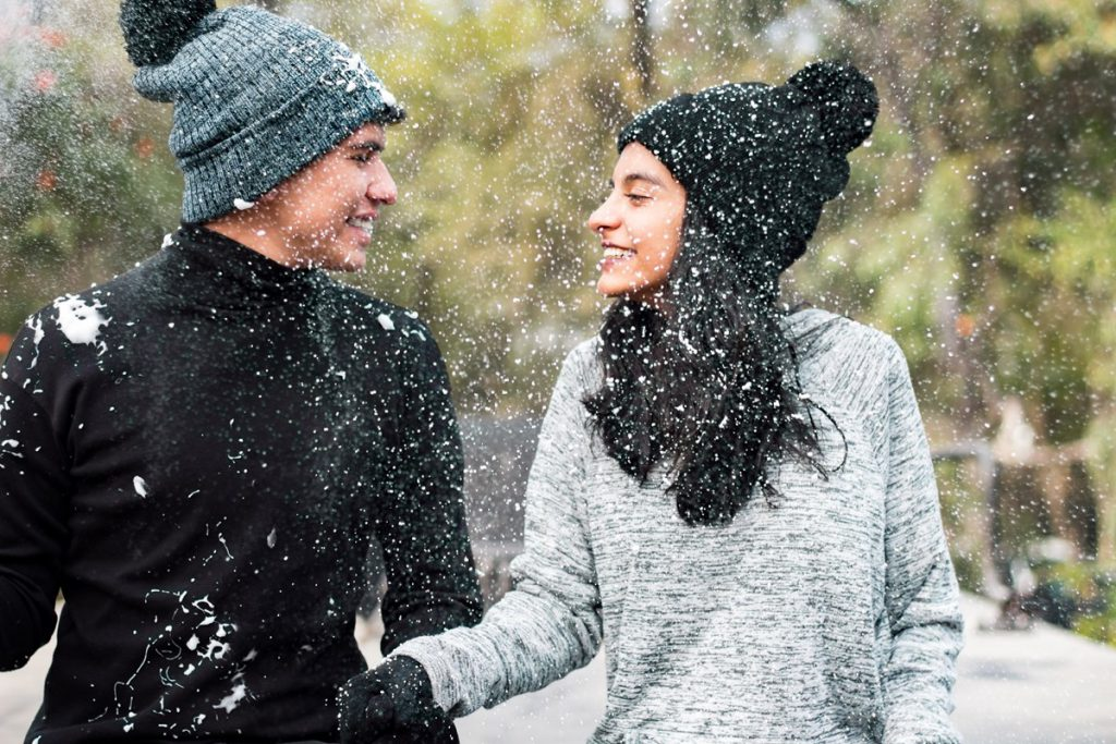 Couple enjoying winter snow in the park