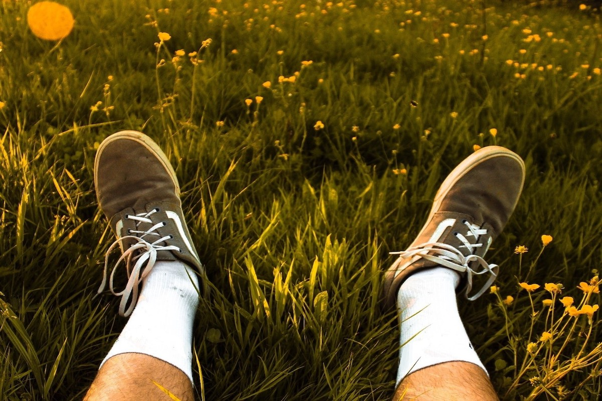 A person lying in the grass on a Summer's day with walking shoes on