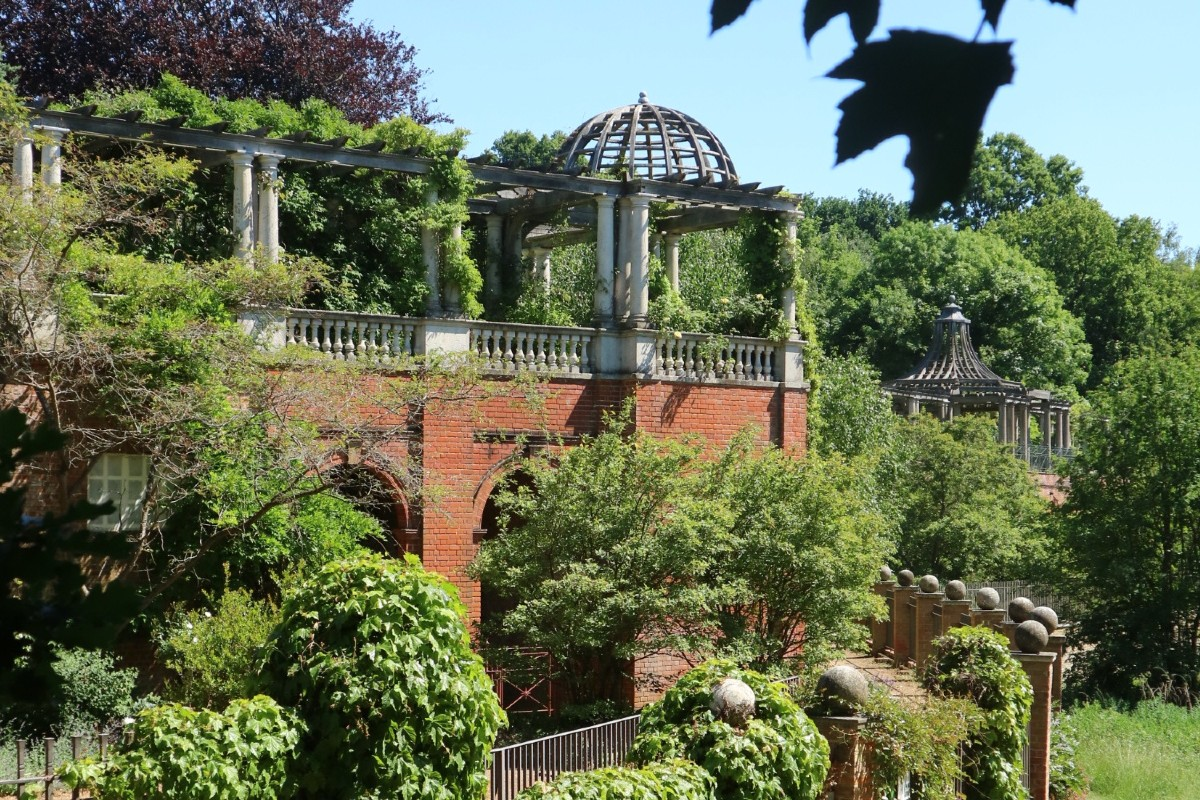 A Georgian arbour and terrace surrounded by trees