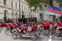 A quadcycle passes Downing street amongst the Cyclists on Whitehall.