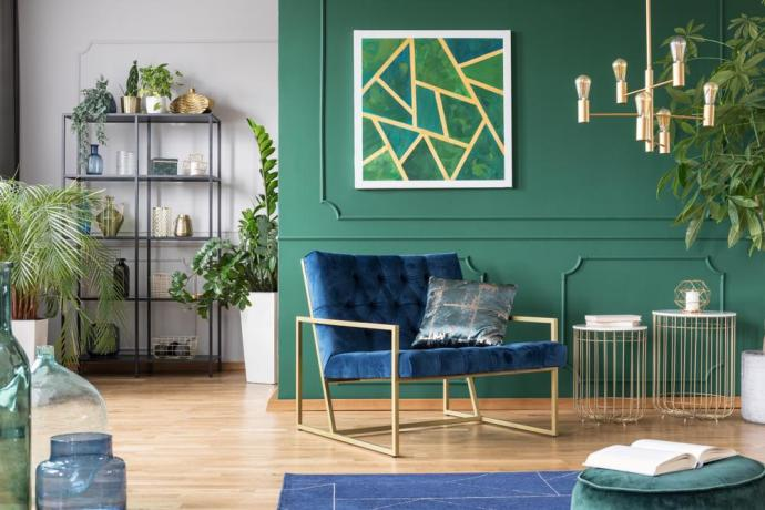 Green painted walls with blue velvet chair