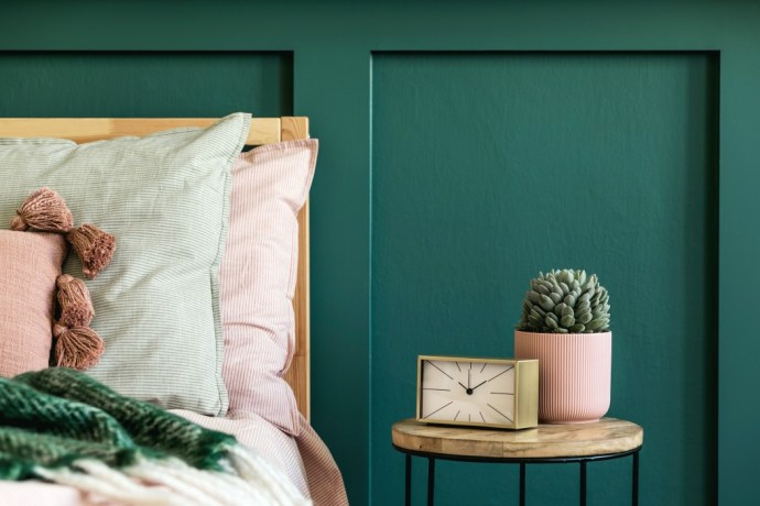 Green panelled wall. Bed with lots of pillows