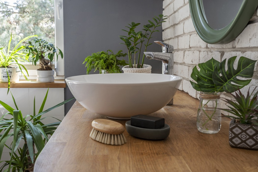 Round bathroom sink on wooden cupboard. Surrounded by plants.