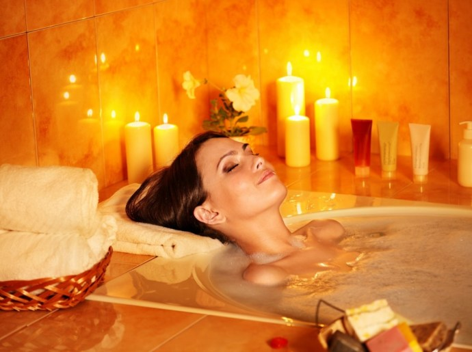 Home Spa. Women laying in bath surrounded by candles