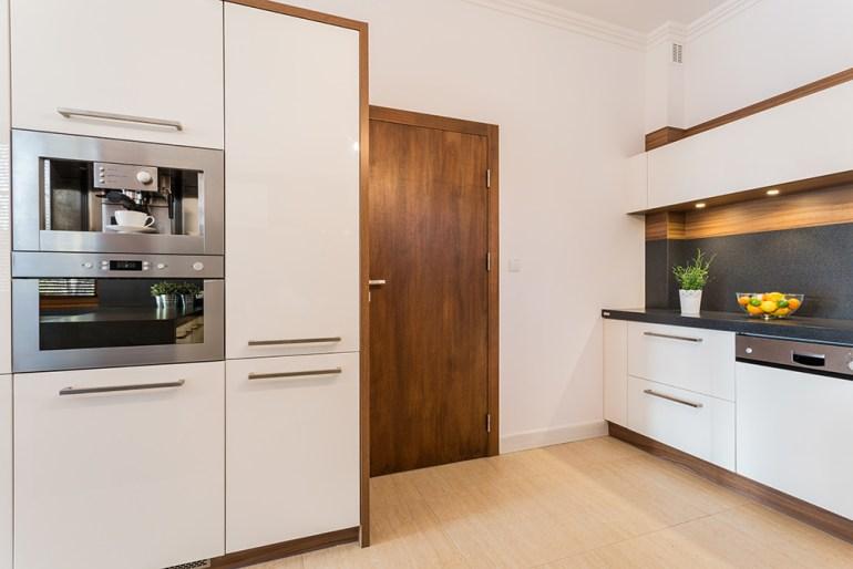 White kitchen with brown kitchen door.