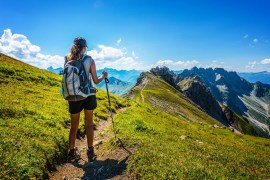 Hiker in boots and backpack holds walking stick while looking at mountings in the distance