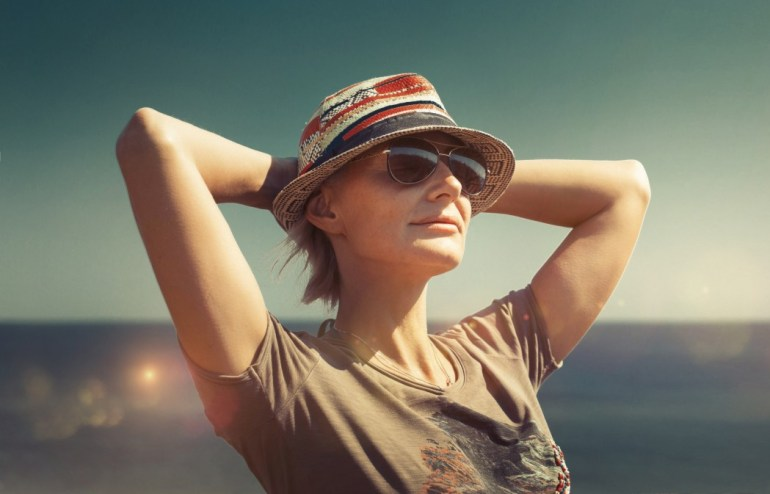 Women with hands behind her head. Wearing sun hat and sun glasses. Relaxing in the sun.