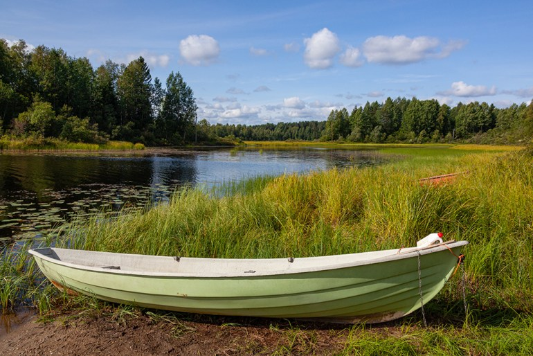 Shabby green boat on the bank of the forest lake, Kainuu region in Finland