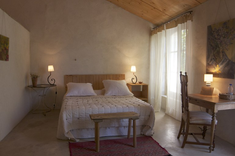 Rustic Bedroom with bare walls and floor and wooden bedroom furniture