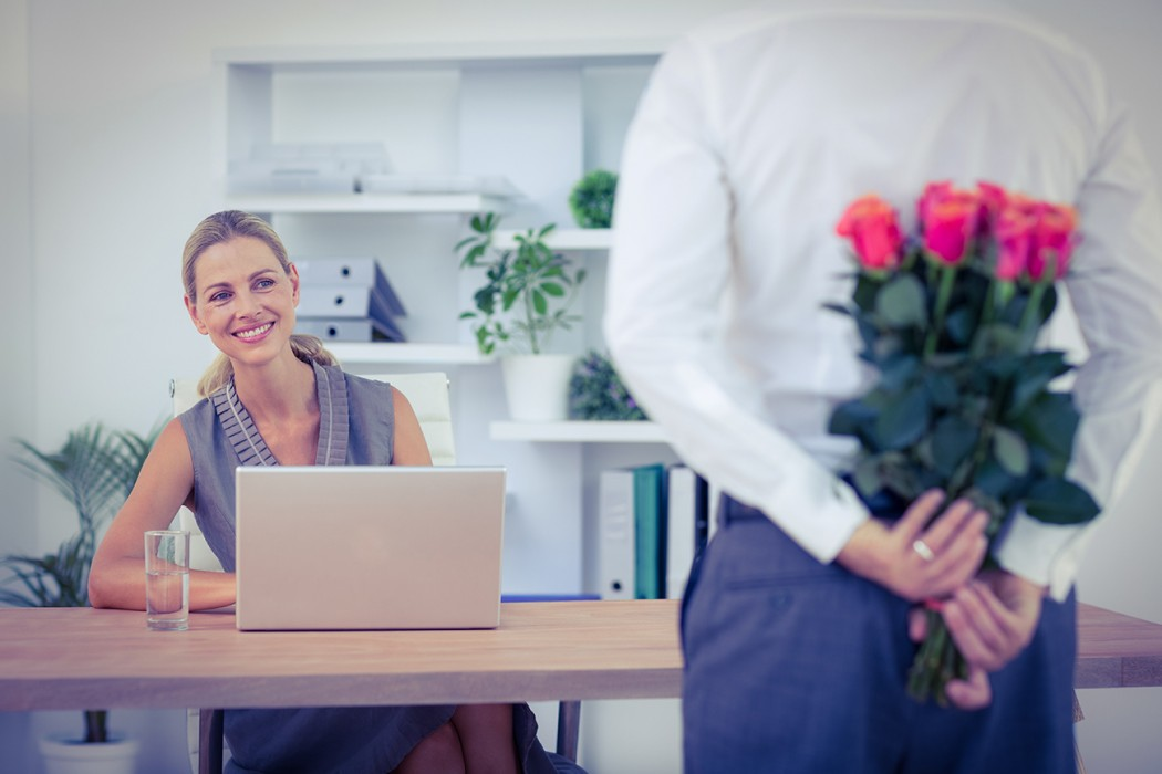 Office romance. Man holding roses behind his back. Women sat at desk with laptop.
