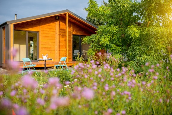 Wooden Summer House surrounded by trees and flowers