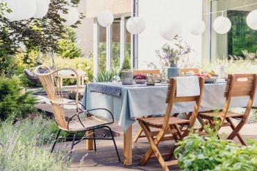 Garden furniture. Garden wooden dining table and chairs. Garden lighting. White paper lantens.