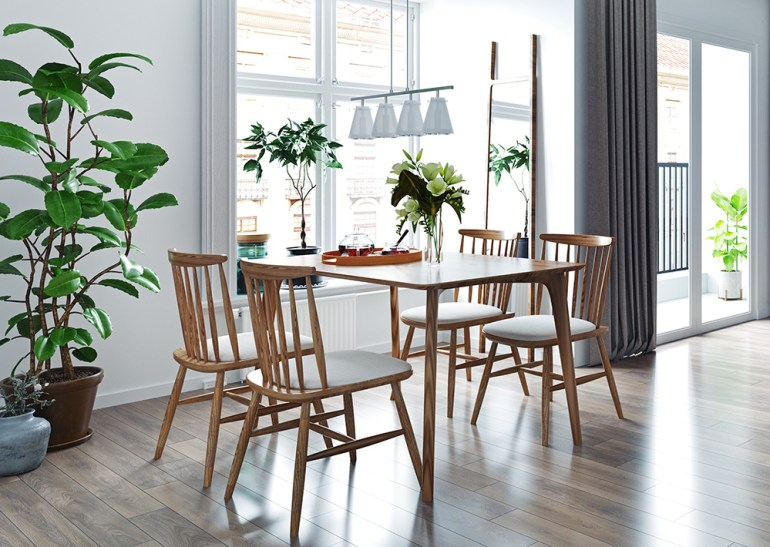 Dining room with plants and  Scandinavian wooden dining table and chairs.