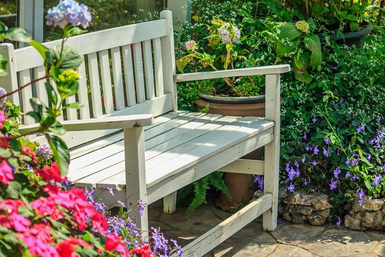 Garden bench surrounded by flowers
