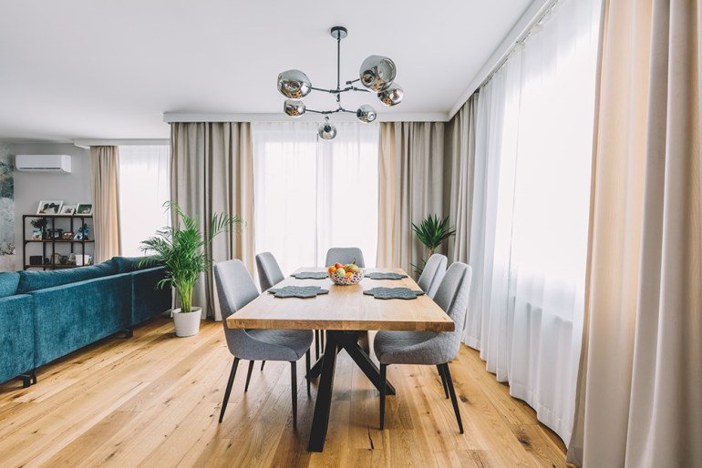 Large living room with dining table and large sofa dividing the room