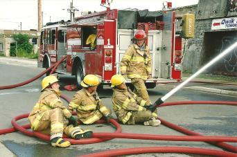 Captain Brian Hanlon supervises Fire Fighters left to right, Bob Hunter, Andrew Contois and Al Arnold