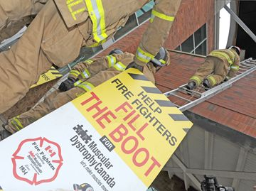 Firefighters climb a ladder to their home for the next three days.