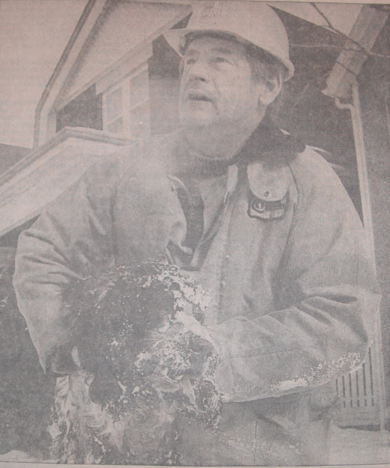 Firefighter holding black spaniel rescued from a house fire.