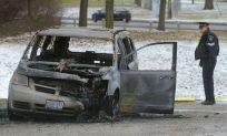 London Police Sgt. Pat Corcoran looks over the burned out remains of a van in a parking lot at Riverside Drive and Wonderland Road on Friday January 27, 2017. MORRIS LAMONT/THE LONDON FREE PRESS /POSTMEDIA NETWORK