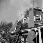 Two Fire Fighters working on a ladder to extinguish a fire within the wall and attic of the second floor of a home.