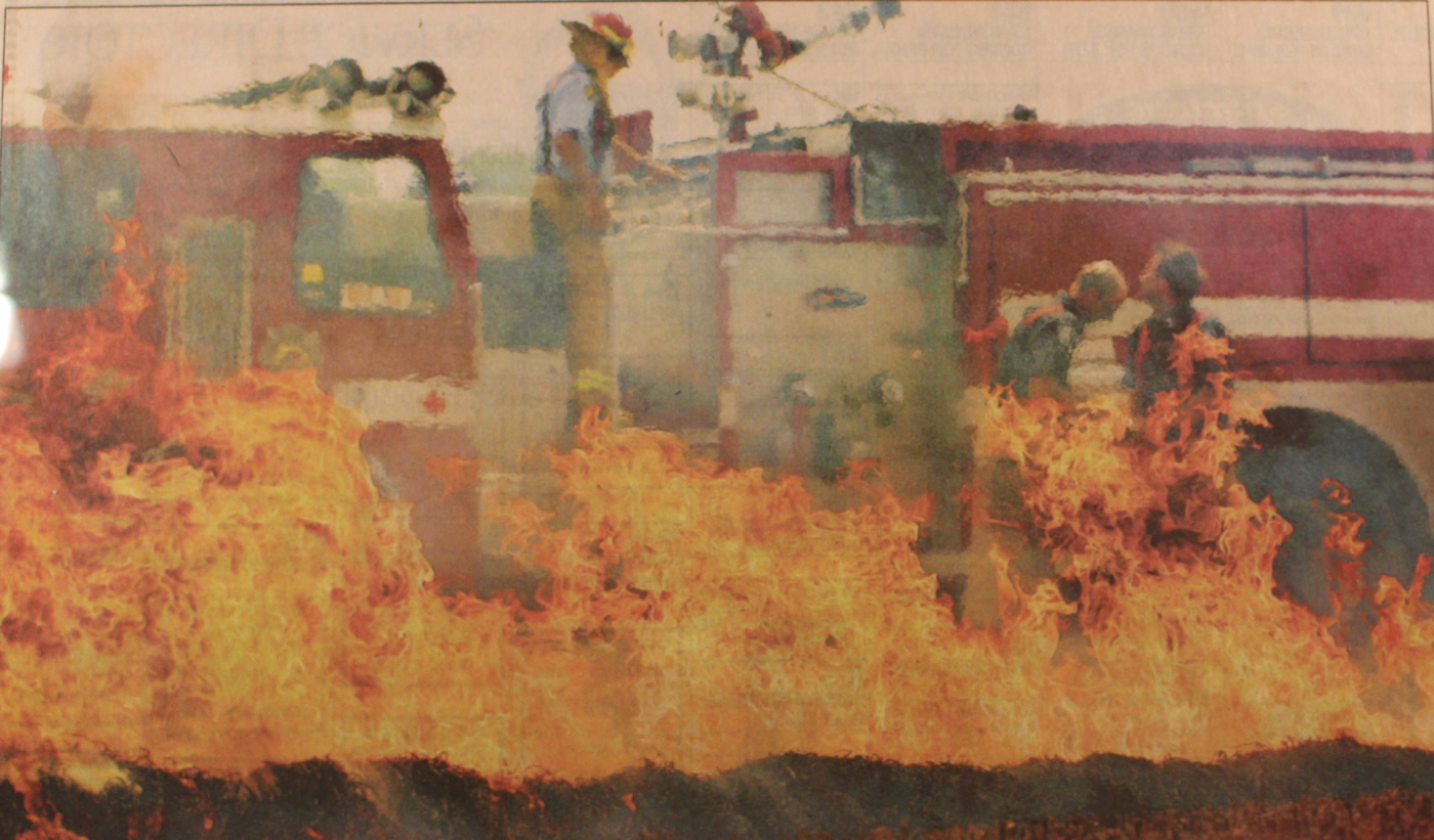 A large grass fire burns with a fire truck and fire fighter in the background, making it appear as they are on fire.
