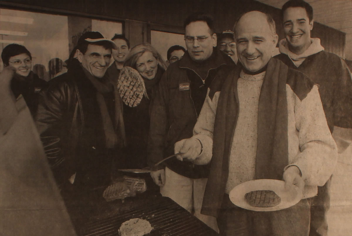Glen Pearson flipping burgers at a barbecue with campaign supporters