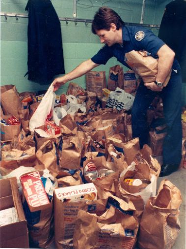 Firefighter David Warren piles up the bags of donated food at London firehall No. 6 on Oxford Street during London's spring food Share-a-thon. (March 26, 1988)