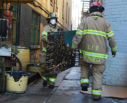 A firefighter removes a piece of art from Artisan's Alley at 430 Richmond St. in London on Wednesday, March 29, 2017. Firefighters were called to a blaze at the downtown building about 4:45 a.m. (DALE CARRUTHERS, The London Free Press)