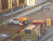 Fire fighters deploying to extinguish car engulfed in flames.