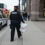 Police officer walking with plastic bucket