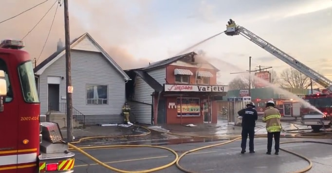 Large fire truck pouring water on burning building