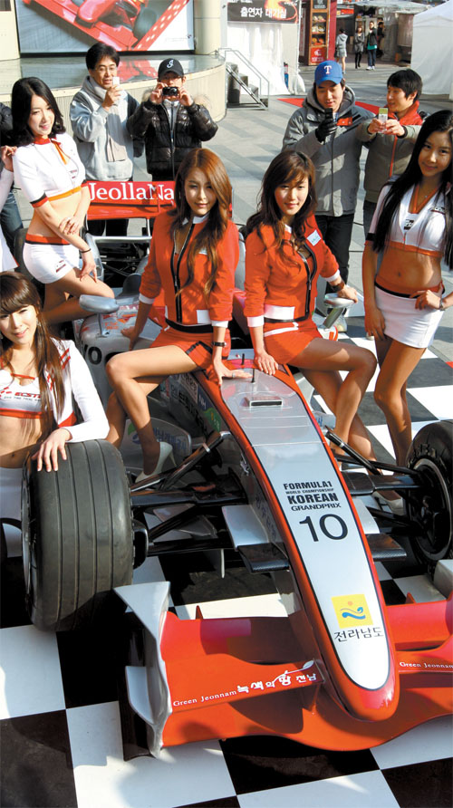 Models pose in front of a Formula One Grand Prix demo car displayed outside of the Goodmorning City shopping mall in Dongdaemun, central Seoul