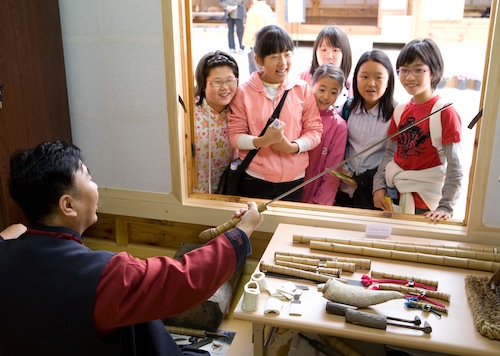 Demonstrating sword-making techniques to children at BICHE 2008