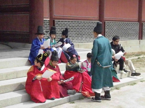 Schoolchildren enter into the spirit of things on the steps of the Injeongmun