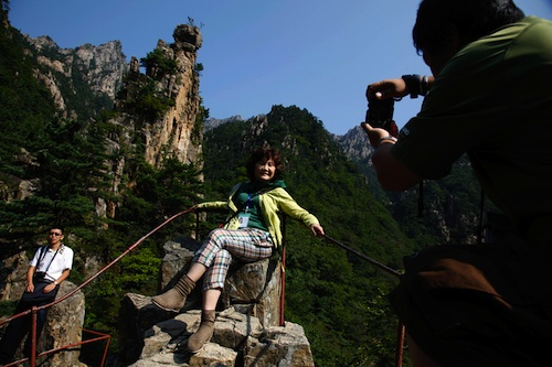 A Chinese tourist poses near mountains peaks at the Kumgang mountain resort