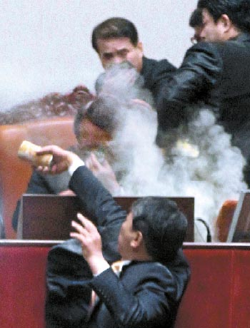 Kim Sun-dong (foreground), a Democratic Labor Party lawmaker, sprays tear gas from a canister at Vice Speaker Chung Ui-hwa in front of the Assembly speaker's podium on 22 November. Nocut News via Joongang Ilbo