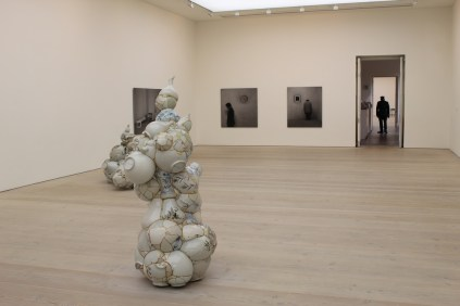 Two of Yeesookyoung's Translated Vase sculptures, with photographs by Hong Seung-hee in the background, in the first room of Korean Eye 2012.
