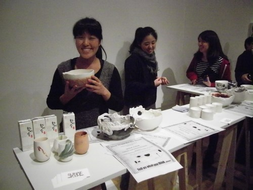 Sunae Kim shows off one of her punch bowls