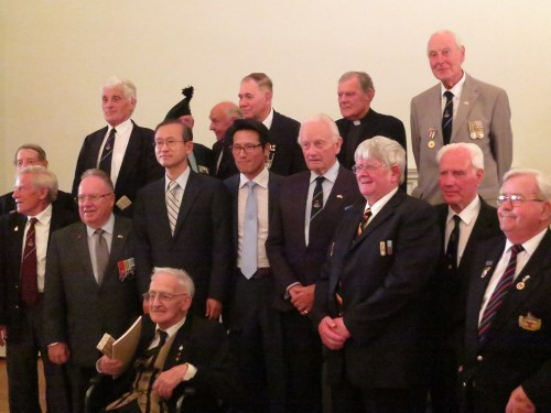 Veterans line up for a team photo with the Ambassador and former Minister of Culture at the opening of A Soldier's Tale