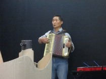 The accordionist accompanies with simple melodies throughout